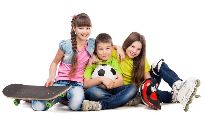 Três crianças bonitos que sentam-se no assoalho com equipamento de esporte foto de stock royalty free