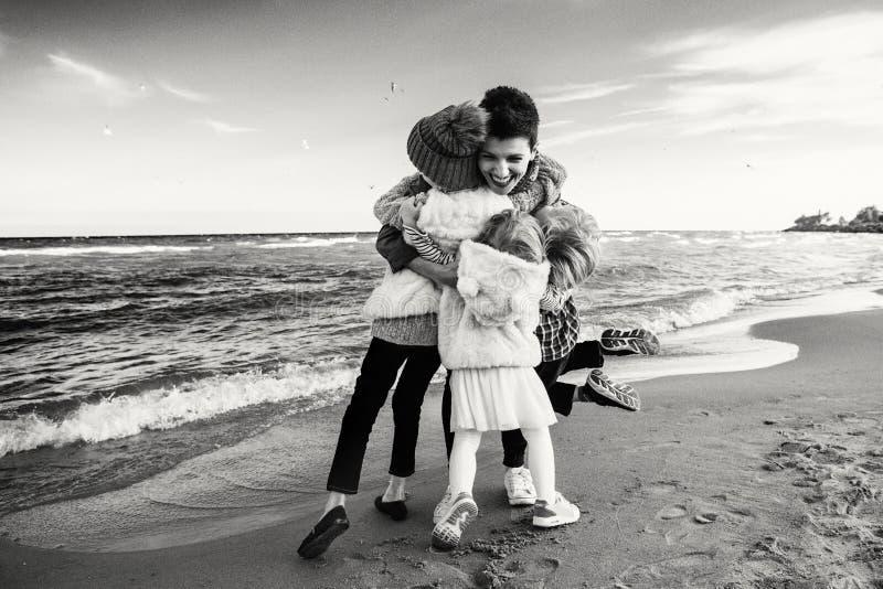 Três crianças caucasianos de riso de sorriso engraçadas caçoam os amigos que jogam a corrida na praia do mar do oceano fotos de stock royalty free
