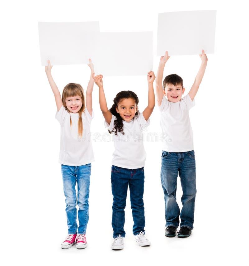 Três crianças cheeerful que guardam a folha de papel vazia do en acima dse foto de stock royalty free