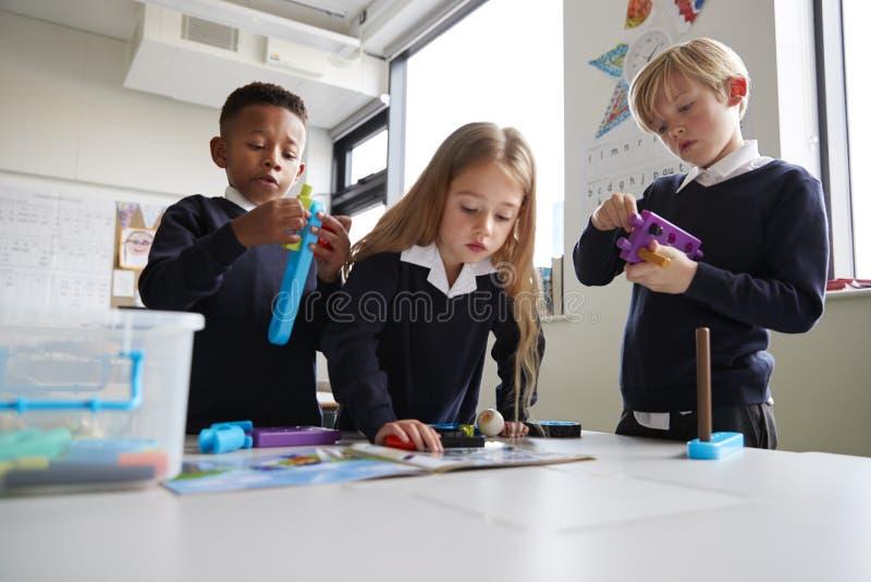 Três crianças de escola primária que trabalham junto com os blocos em uma sala de aula, as instruções de leitura da construção do foto de stock