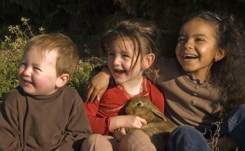 Três crianças e coelhos foto de stock