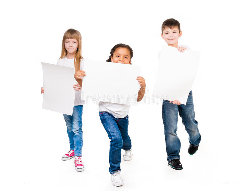 Três crianças engraçadas que guardam as placas de papel nas mãos foto de stock