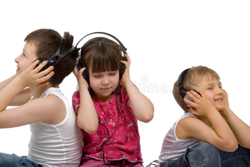 Três crianças escutam a música fotos de stock