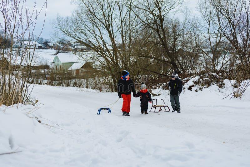 Três crianças estão arrastando o trenó na montanha fotografia de stock royalty free