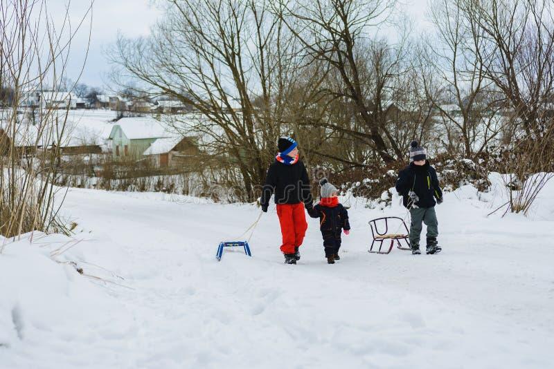 Três crianças estão arrastando o trenó na montanha imagens de stock royalty free