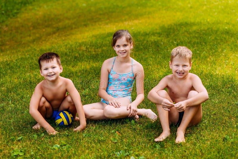 Três crianças felizes alegres nos maiôs sentam-se na grama verde e no olhar na câmera fotos de stock royalty free