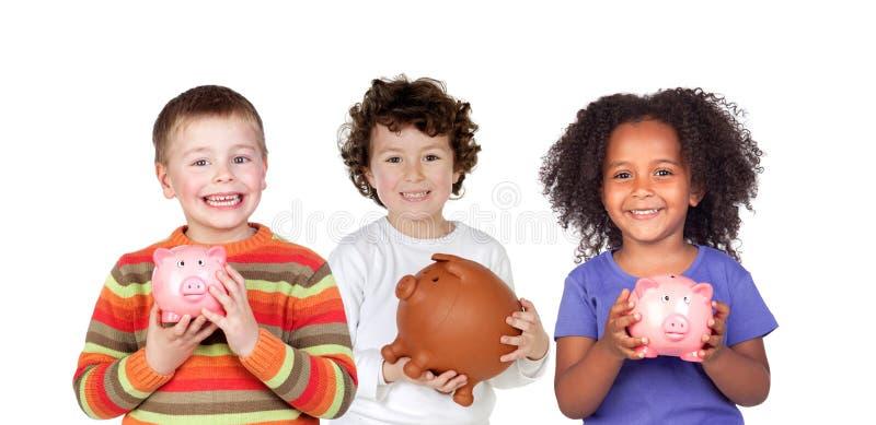 Três crianças felizes com mealheiros fotografia de stock