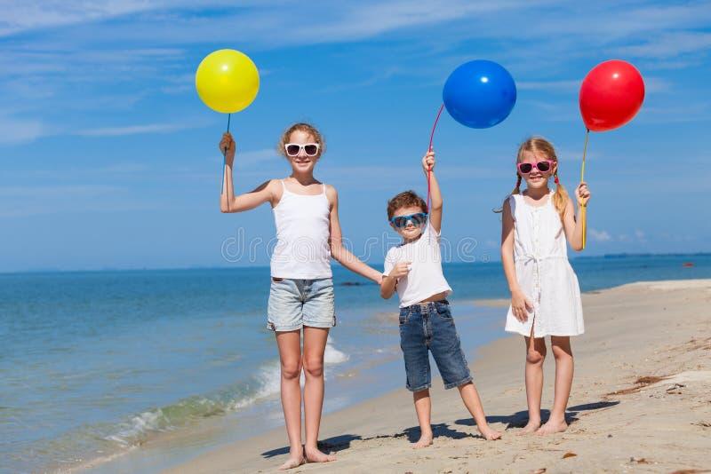 Três crianças felizes com os balões que estão na praia no imagem de stock