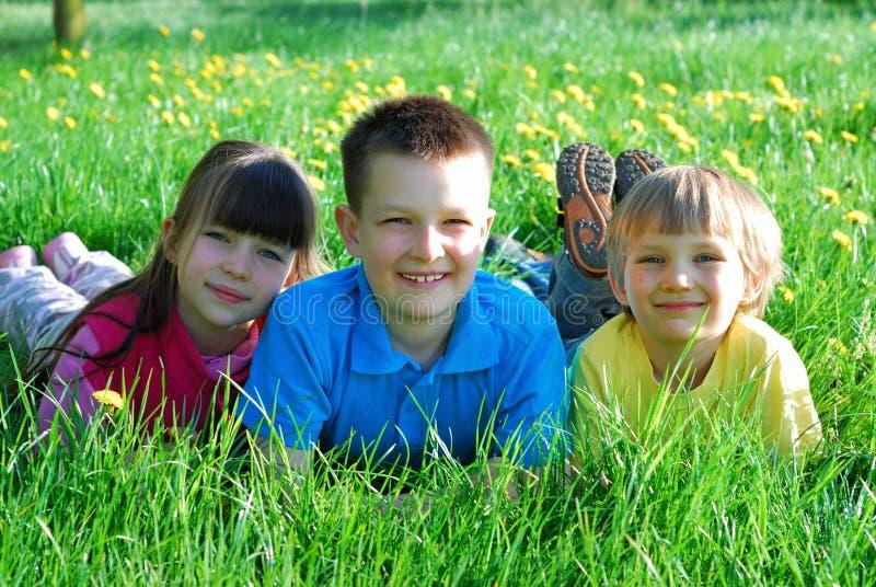 Três crianças felizes no prado fotos de stock