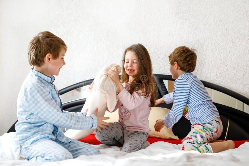Três crianças felizes nos pijamas que comemoram o partido de pijama Pré-escolar e meninos e menina de escola que têm o divertimen foto de stock