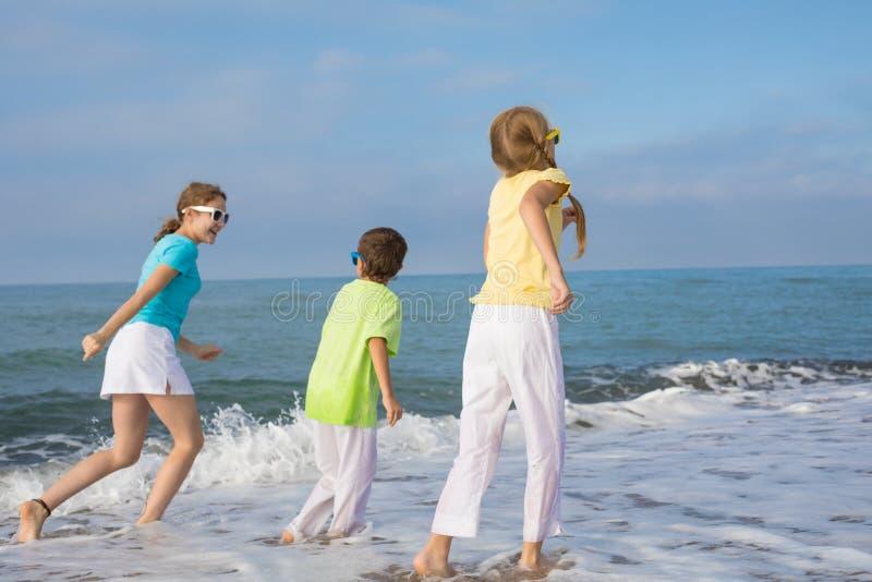 Três crianças felizes que correm na praia no tempo do dia imagem de stock royalty free