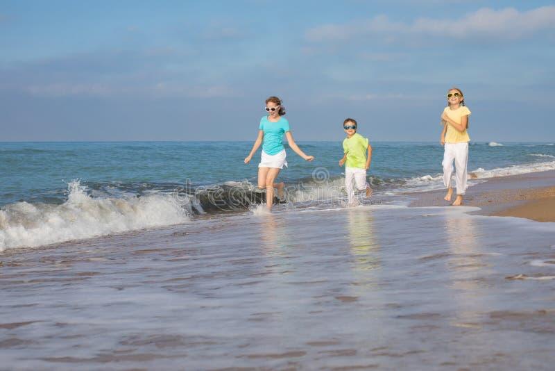 Três crianças felizes que correm na praia no tempo do dia fotografia de stock