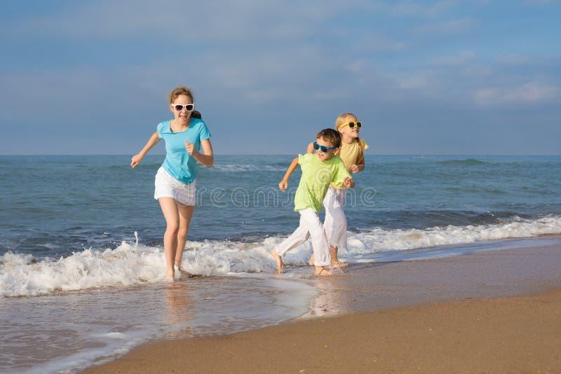 Três crianças felizes que correm na praia no tempo do dia imagens de stock royalty free