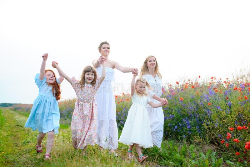Três crianças felizes que correm no campo no tempo do dia Conce imagens de stock royalty free