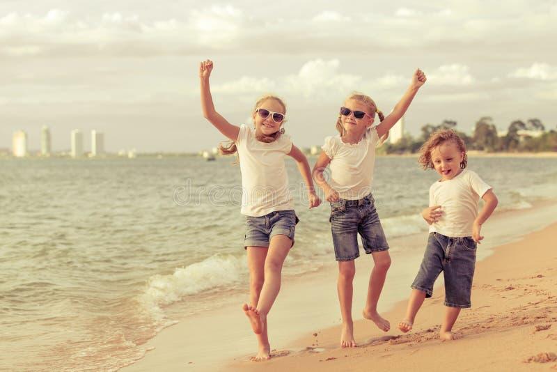 Três crianças felizes que dançam na praia foto de stock