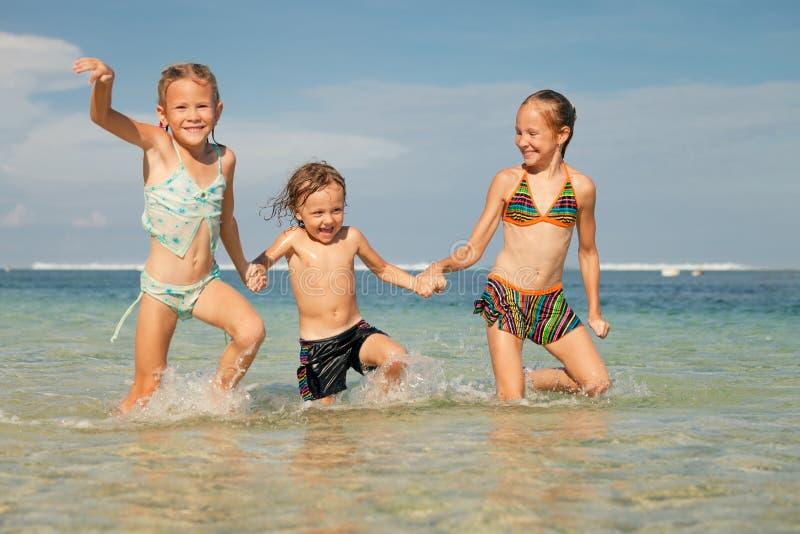Três crianças felizes que jogam na praia imagem de stock royalty free