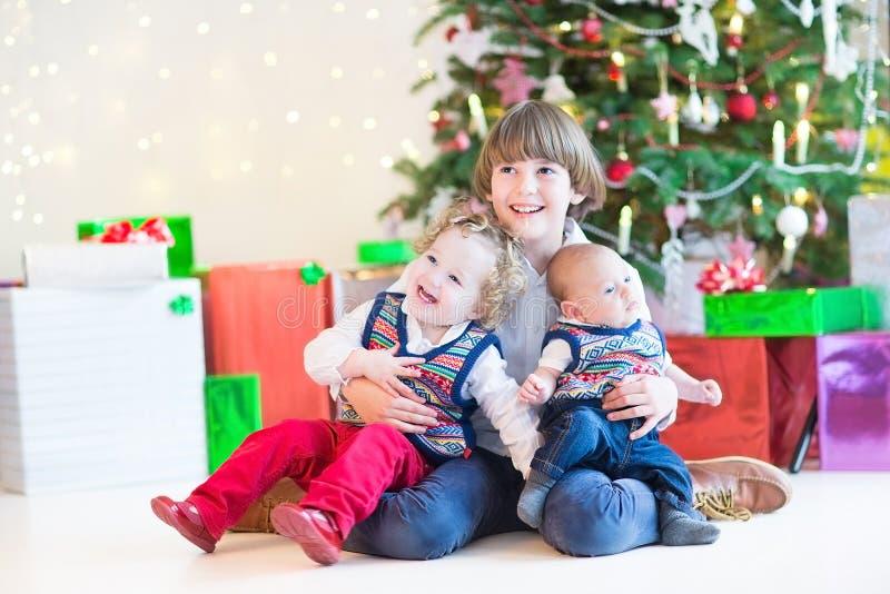 Três crianças felizes sob a árvore de Natal bonita fotos de stock