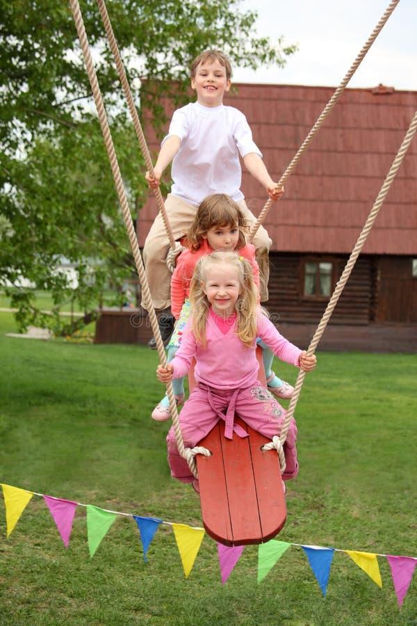 Três crianças na teetering-placa fotografia de stock royalty free