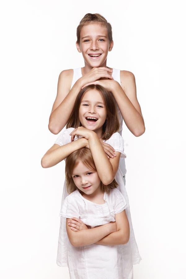 Três crianças no estúdio em fundo branco, um irmão e duas irmãs riem foto de stock