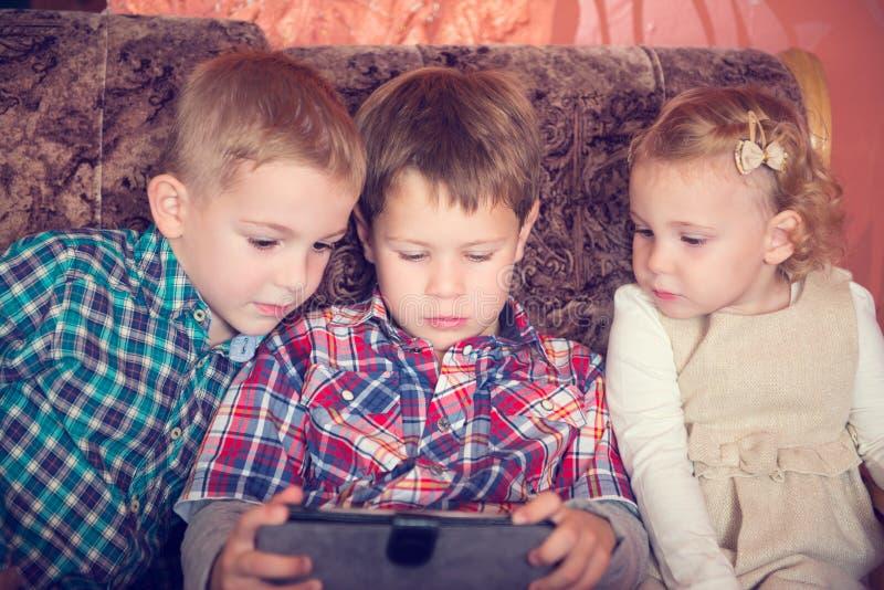 Três crianças pequenas que jogam com PC da tabuleta imagem de stock royalty free