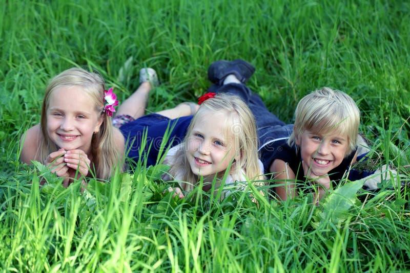Três crianças que encontram-se na grama verde no parque imagem de stock
