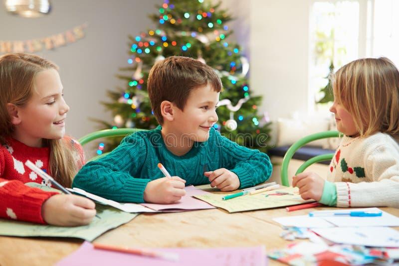 Três crianças que escrevem letras a Santa Together imagem de stock royalty free