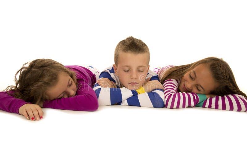 Três crianças que estabelecem nos pijamas que falsificam o sono imagem de stock royalty free