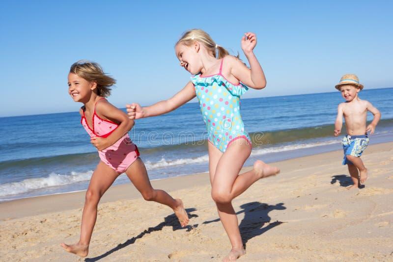 Três crianças que funcionam ao longo da praia fotografia de stock royalty free