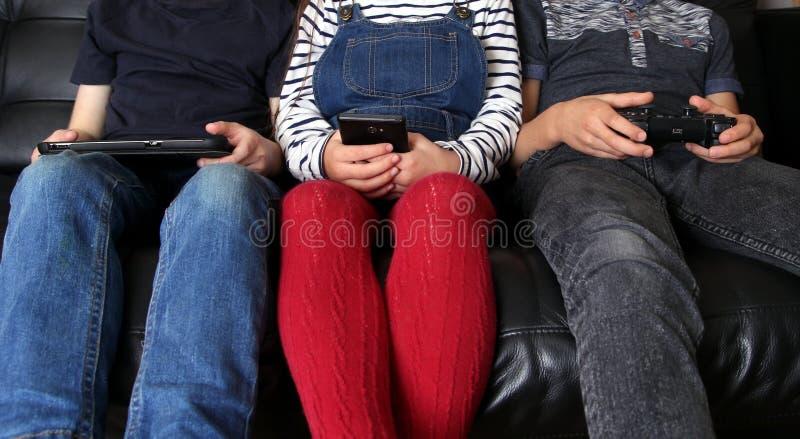 Três crianças que jogam com dispositivos eletrónicos - tabuleta, smartph imagem de stock