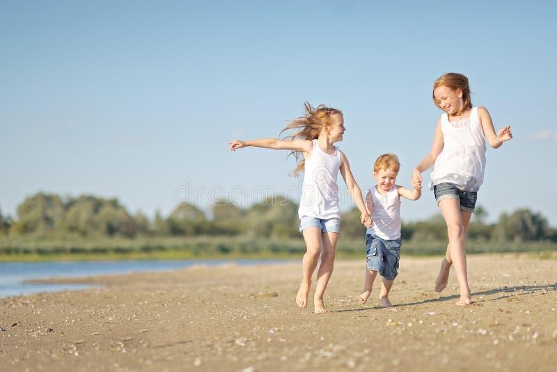 Três crianças que jogam na praia imagens de stock
