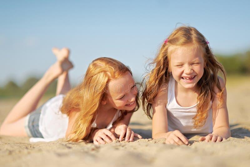 Três crianças que jogam na praia imagens de stock royalty free