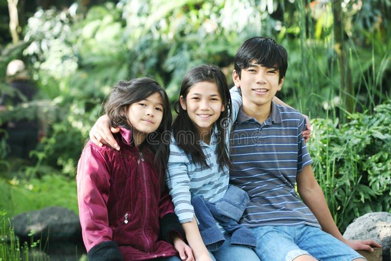 Três crianças que sentam-se ao ar livre fotografia de stock royalty free