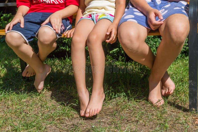 Três crianças que sentam-se junto no banco fotografia de stock royalty free