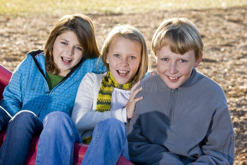 Três crianças que sentam-se na corrediça imagens de stock
