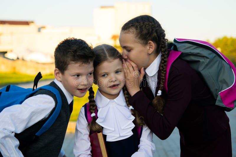 Três crianças sussurram-se na orelha e no riso, após lições da escola fotos de stock