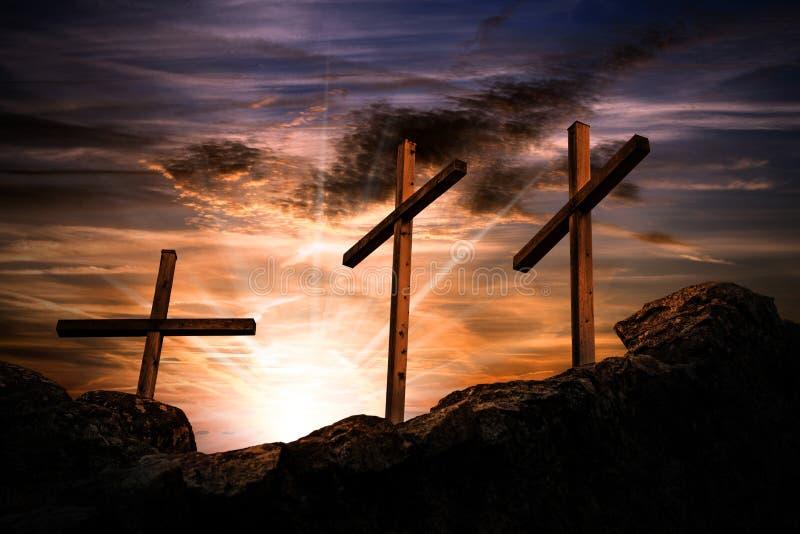Três cruzes em um céu dramático no por do sol fotografia de stock