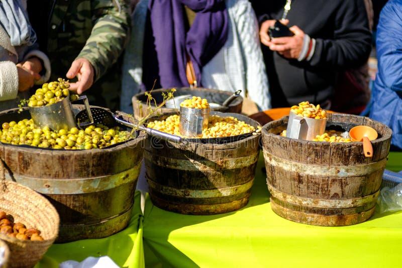 Três cubetas velhas com lupine e azeitonas em um mercado português foto de stock