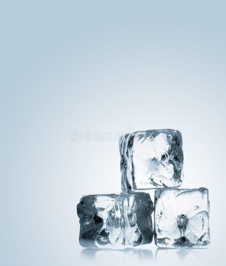 Três cubos de gelo empilhados sobre o fundo azul do inclinação imagens de stock