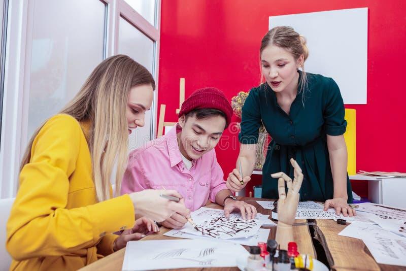 Três desenhadores de moda do futuro que têm a discussão em grupo imagens de stock