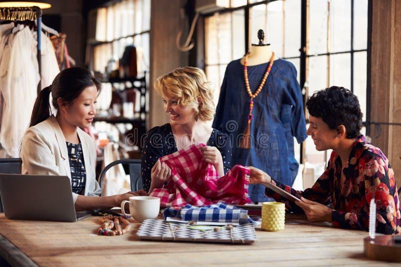 Três desenhadores de moda na reunião que discutem matérias têxteis imagens de stock royalty free
