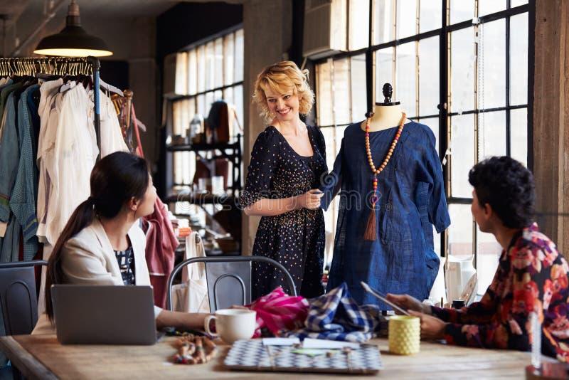 Três desenhadores de moda na reunião que discutem o vestuário fotografia de stock royalty free