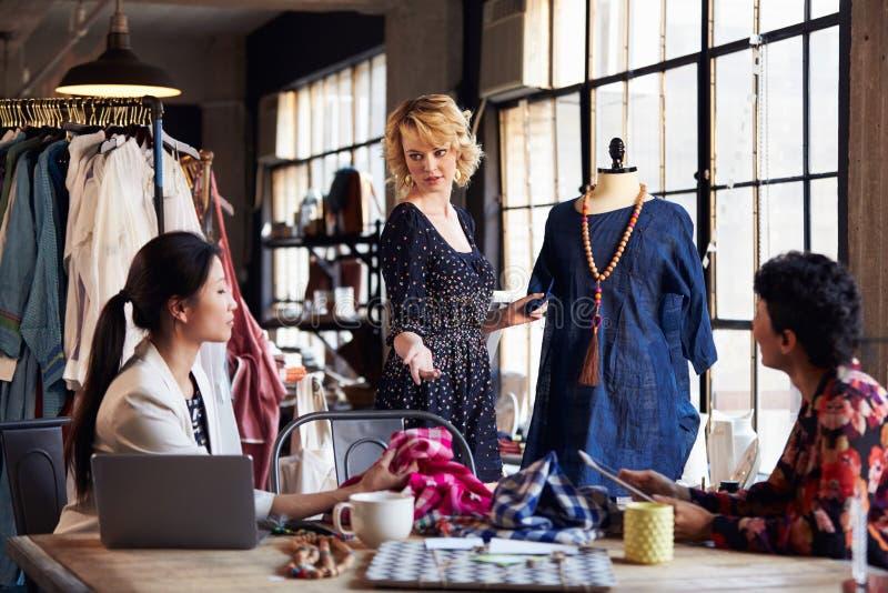 Três desenhadores de moda na reunião que discutem o vestuário imagens de stock