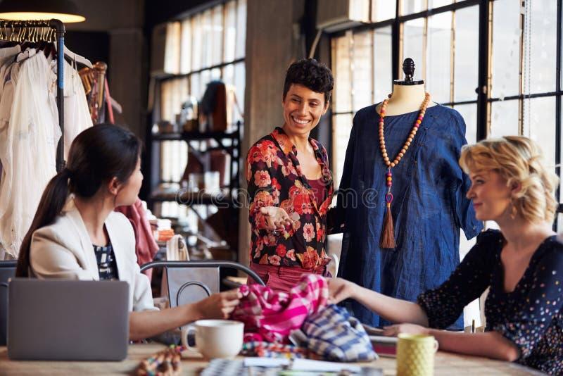 Três desenhadores de moda na reunião que discutem o vestuário imagem de stock royalty free