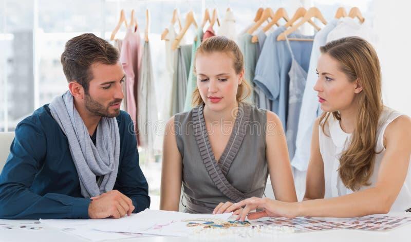 Três desenhadores de moda que discutem projetos foto de stock royalty free