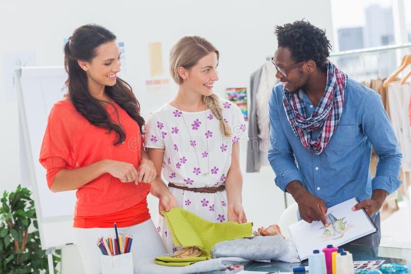 Três desenhadores de moda que olham o bloco de notas imagens de stock