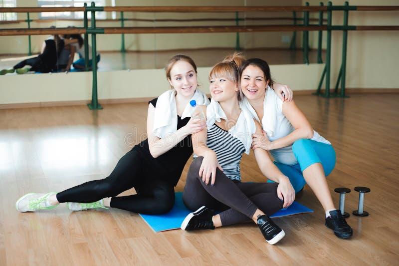 Três desportistas alegres que riem e que têm o divertimento após o exercício no gym A fêmea bonito toma um resto após o exame dur imagens de stock
