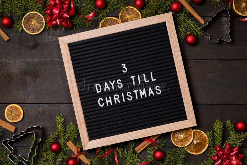 Três dias até a placa da letra da contagem regressiva do Natal na madeira rústica escura imagens de stock