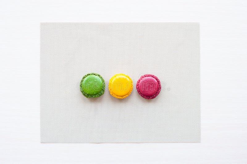 Três diferente-coloriram em volta das cookies francesas do macaron na tabela imagem de stock royalty free