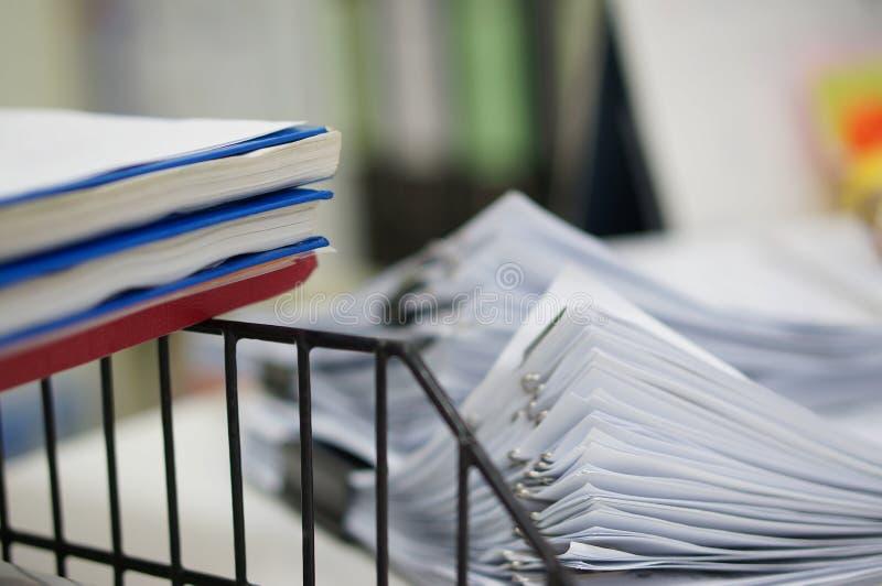 Três do caderno do relatório na cremalheira preta da prateleira e da pilha dos papéis brancos dos dados cobrem fotos de stock