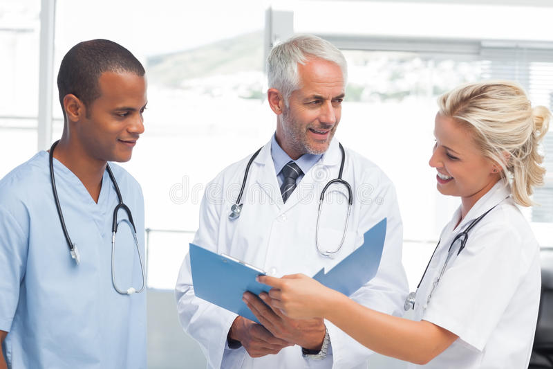 Três doutores de sorriso que examinam um arquivo imagens de stock royalty free